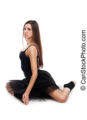 female ballet dancer in black dress with beautiful healthy brown long hair lying on white background