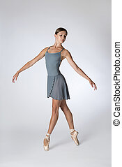 Female Ballet Dancer in Gray Leotard En Pointe
