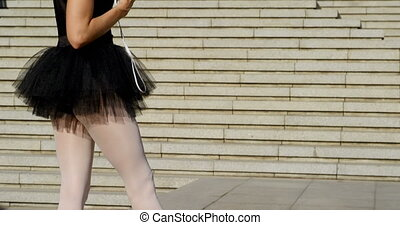 Female ballet dancer listening music on mobile phone 4k -...