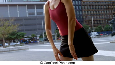 Female ballet dancer performing on pavement in the city 4k -...