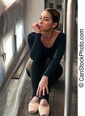 Female ballet dancer sitting against window
