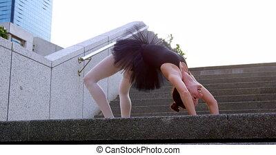 Female ballet dancer stretching on the stair 4k - Female...