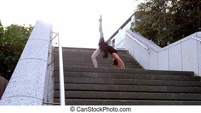 Female ballet dancer stretching on the steps 4k - Female...