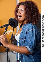 Female Band Member Singing In Recording Studio