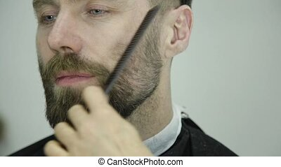 Female barber cuts clients beard with a professional beard...