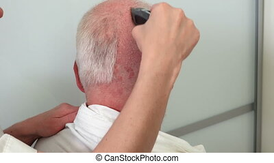 Female barber cutting hair with clipper on a man with...