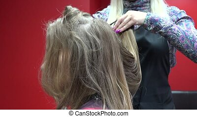 Female barber hands trimming customer blond hair tips with...