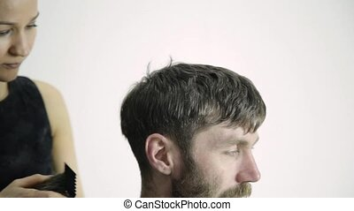 Female barber shaping men's haircut with clipper in the...
