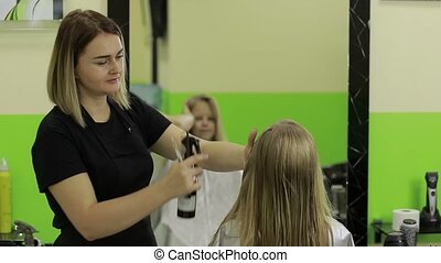 Female barber spraying water on client's hair