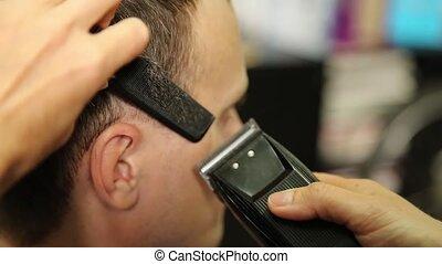 female barber using a clipper to cut a mans hair - female...