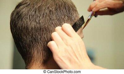 female barber using a scissors to cut a mans hair