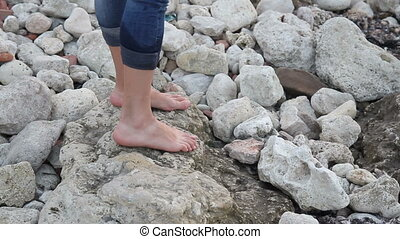 Female bare feet step on stones on the shore