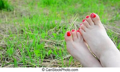 Female bare legs with red pedicure on grass