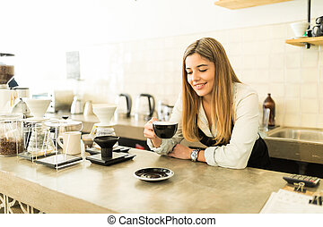 Female barista enjoying a cup of coffee