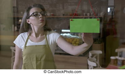Female barista with glasses looking out the window for clients sighing tiered at the end of shift and flipping over green screen closing sign