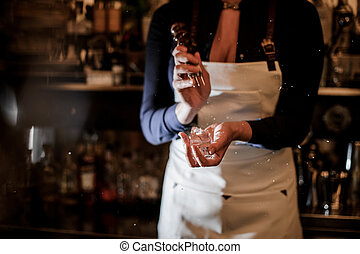 Female barman crushing a piece of ice for making a cocktail...