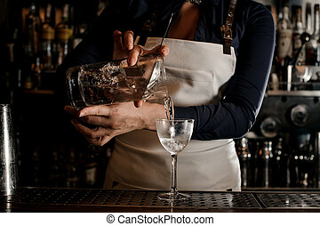 Female barman hand pouring fresh cocktail into a glass -...