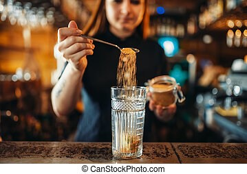 Female barman mixing at the bar counter in pub