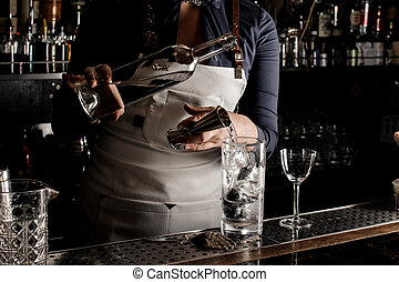 Female barman pouring gin into a cocktail glass - Female...