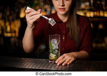 Female bartender adding an ice with tongs to the cocktail