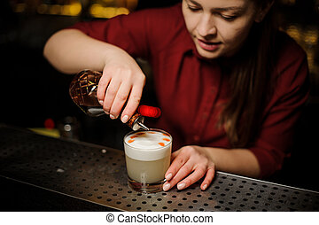 Female bartender making a final preparing for serving a delicious white cocktail