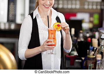 Female bartender making a fruit cocktail