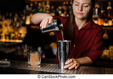 Female bartender making cocktail at the bar counter