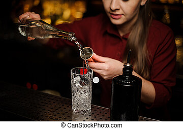 Female bartender pouring gin into a cocktail glass
