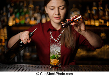 Female bartender pouring out a transparent alcoholic drink from the measuring pile with splash