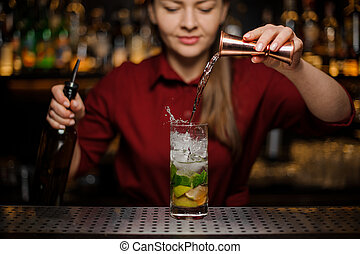 Female bartender pouring out a transparent drink from the measuring pile with splash