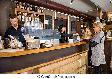 Female Bartender Serving Coffee To Customer At Counter -...