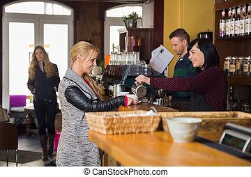 Female Bartender Serving Coffee To Woman - Female bartender...