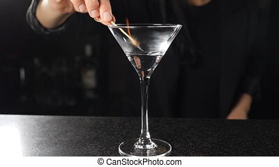 Female bartender setting fire with burning stick on alcohol cocktail in slow motion. Fire ignition on drink with spirit. Flames in transparent glass. Bar counter on black background. Full hd footage