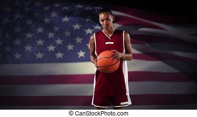 Female basketball player against waving US flag