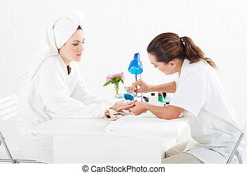 beautician applying manicure - female beautician applying...