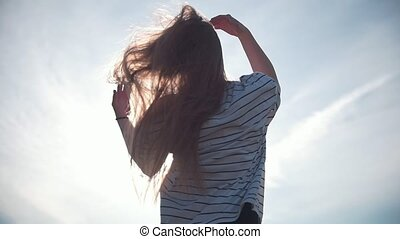 Female beautiful long hair flying in the wind at sunset