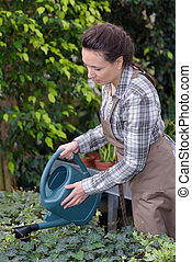 female beauty watering her plants outside