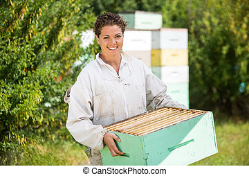 Female Beekeeper Carrying Honeycomb Crate - Portrait of...
