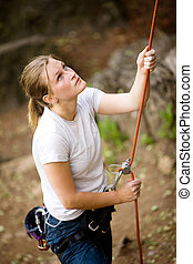 Female Belayer - A female belaying a male on a steep rock ...