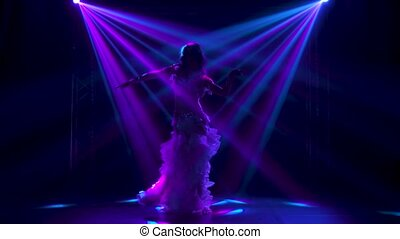Female belly dancer in a white oriental costume shaking her hips. Shot in a dark studio with smoke and neon lighting. Silhouettes of a slender flexible body