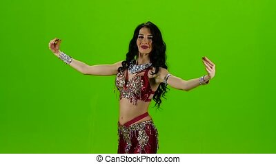 Female belly dancer who is starting shaking her hips. Green...