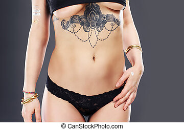 Female belly with tattoo