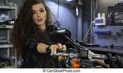 Female biker shakes her hair on the motorcycle