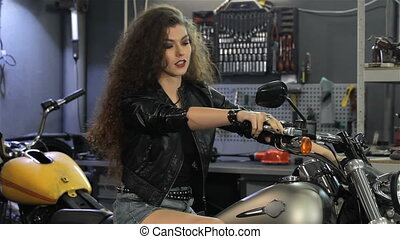 Female biker shows her thumb up on the motorcycle