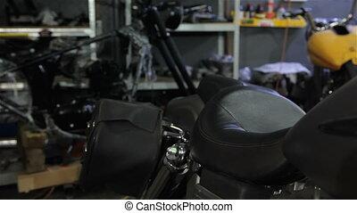 Female biker squats near the motorcycle