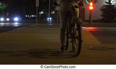 Female biker standing at red light on crosswalk. Traffic light. 4K shot