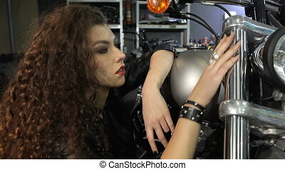 Female biker touching the front fork of motorcycle - Pretty...