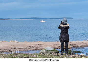Female bird watcher by the coast in early springtime on the ...