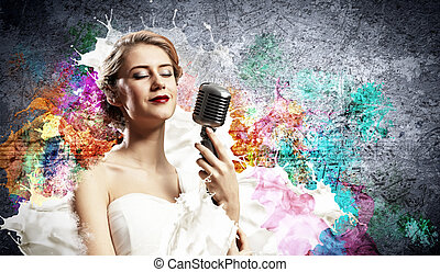 Female blonde singer - Image of female blonde singer holding...