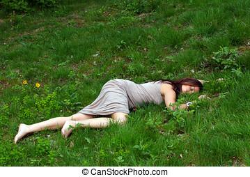 Female body lying in grass - Woman\'s body lying in a grass...